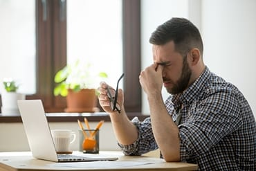 Man with headache at computer featured
